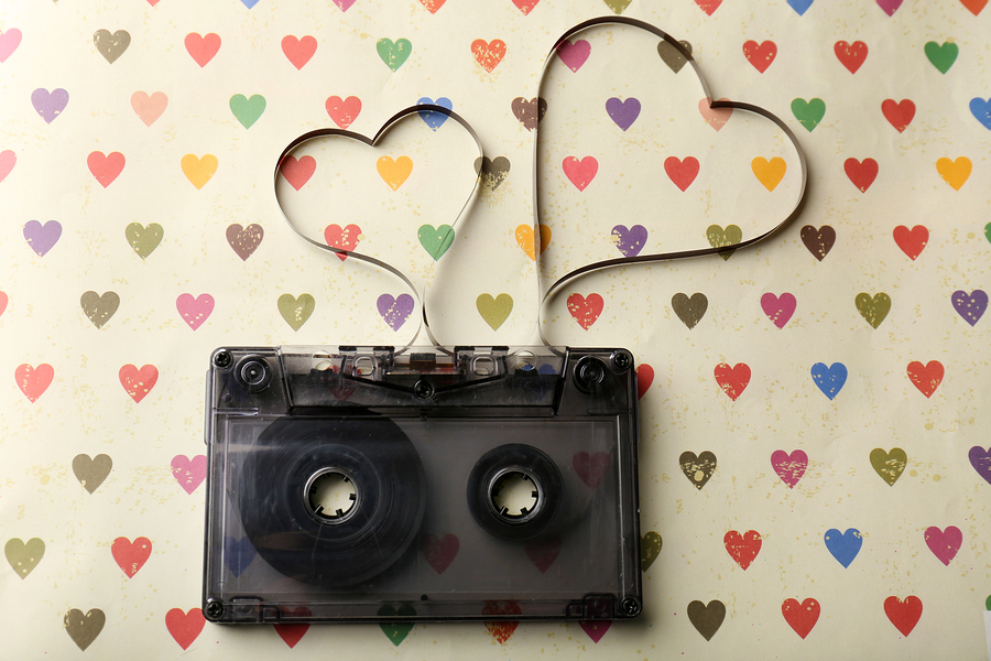 Audio cassette with magnetic tape in shape of hearts on paper ba