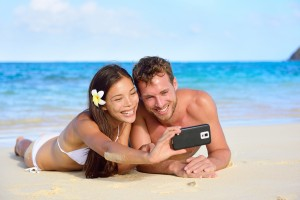 Beach holiday couple taking selfie with smartphone lying down re