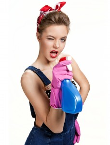 Beautiful cleaning girl wearing pink rubber protective gloves holding spray / young beautiful American pin-up girl isolated on white background. Cleaning service concept