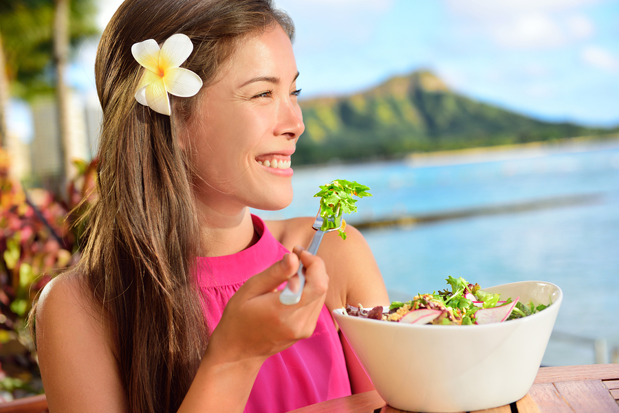Salad eating healthy woman at restaurant in Hawaii. Asian Multiracial young female adult sitting at beach cafe eating a vegetarian lunch meal during summer vacations in Waikiki, Honolulu, Hawaii, USA.