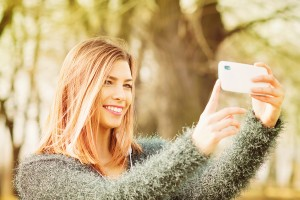 Young blonde woman taking a selfie outdoors
