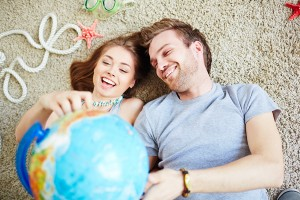 Young couple with globe dreaming of summer vacations
