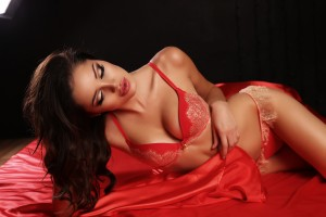fashion interior photo of sexy beautiful woman with dark hair in red lace lingerie lying on silk sheet in bedroom