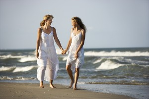 Caucasian mother and pre-teen girl walking on beach holding hand
