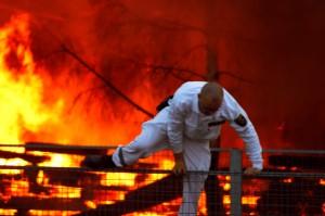 closeup of a man running away from burning building