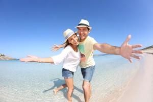 Happy couple walking in crystal clear sea water