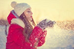 Beauty Winter Girl Blowing Snow in frosty winter Park. Outdoors.
