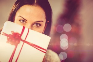 Pretty brunette holding christmas present at home in the living