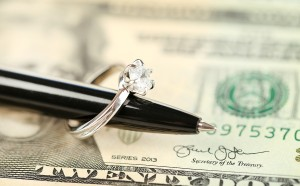Wedding ring on pen, on banknotes background. Marriage of conven