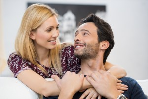 Young couple looking at each other hugging in living room. Happy