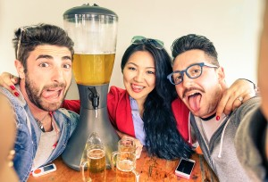 Happy Friends Taking Selfie With Funny Tongue Out Near Beer Towe