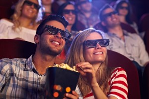 Happy couple sitting in movie theater, watching 3D movie, eating
